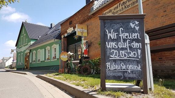 Eine Infotafel vor einem grünen Gassthof.