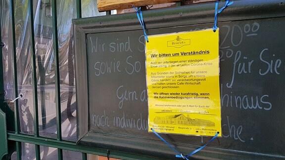 Ein gelbes Infoblatt hängt an einem Eingangstor.