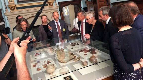Menschen stehen in einem Museum an einer Vitrine mit Kunstobjekten