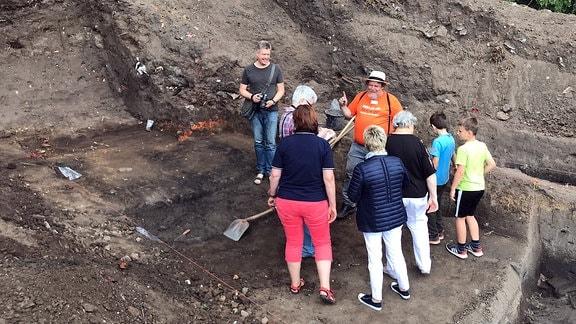Archäologe und Projektleiter Louis D. Nebelsick im orangen Shirt mit Besuchern im Ausgrabungsgelände Kemberg