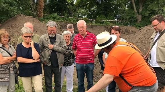 Archäologe und Projektleiter Louis D. Nebelsick im orangen Shirt zeigt Besuchern Ausgrabungsfunde von Kemberg