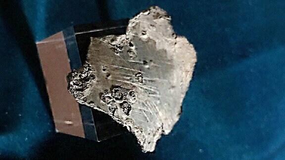 Ein Stück Zink von Luthers Grab auf dunkelblauem Stoff.