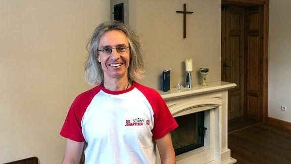 Christian Gatniejewski, ein Mann in rot-weißem T-Shirt und mit schulterlangen grauen Haaren, lächelt in die Kamera