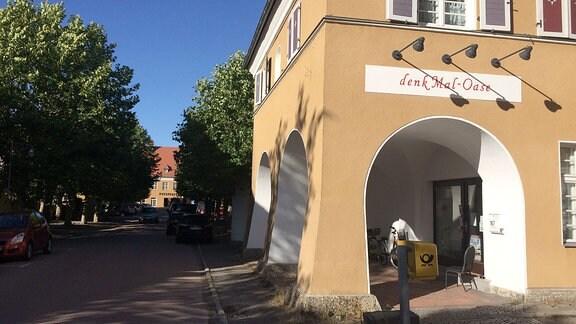 Ockerfarbenes Haus mit Aufschrift ''denkMal Oase''.