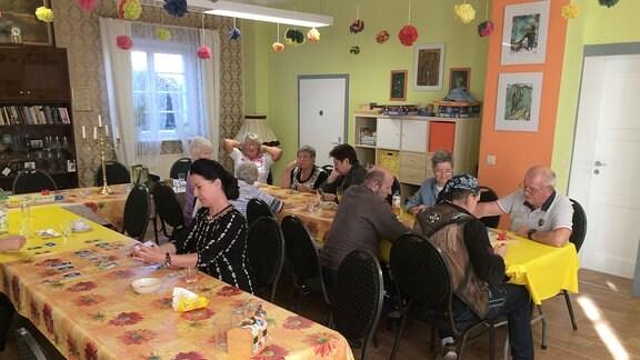 Menschen sitzen in geschmücktem Raum an langen Tischen.