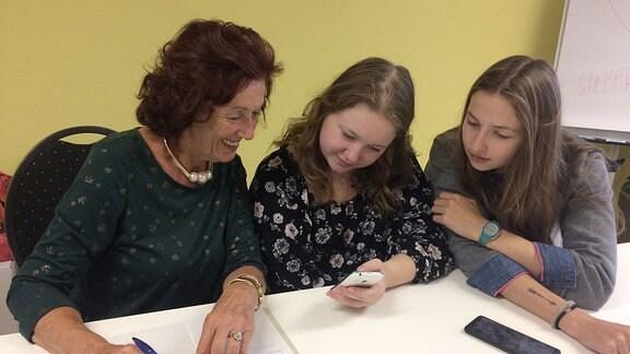 Zwei junge Mädchen und eine ältere Frau sitzen mit Handy an einem Tisch.