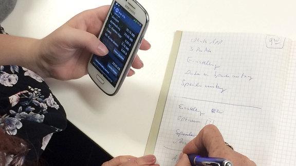 Hand hält Handy, daneben werden Notizen gemacht.