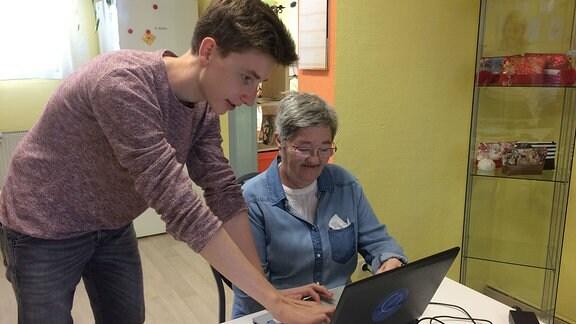 Jugendlicher steht neben älterer Frau, die an Tisch mit Laptop sitzt.