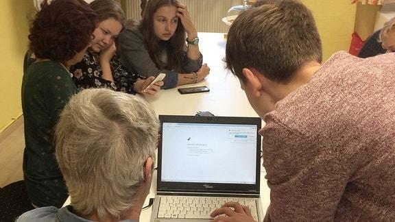 Jugendliche sitzen mit älteren Leuten am Tisch und erklären Handy und Laptop.