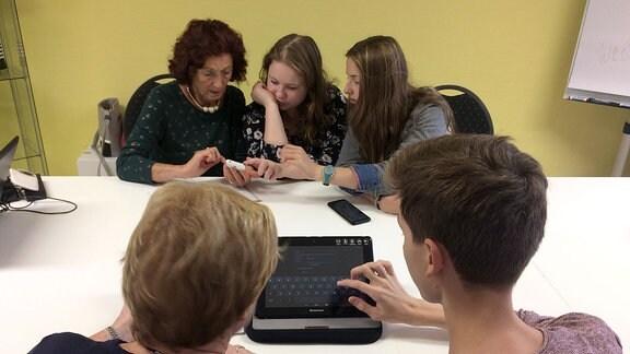 Jugendliche sitzen mit älteren Frauen am Tisch und erklären Handy und Tablet.