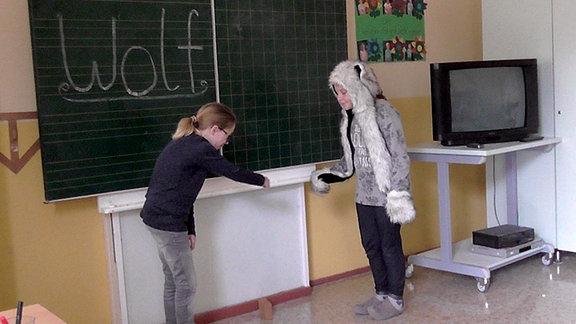 Zwei Schüler imitieren eine Wolfsbegegnung vor einer Tafel im Klassenzimmer