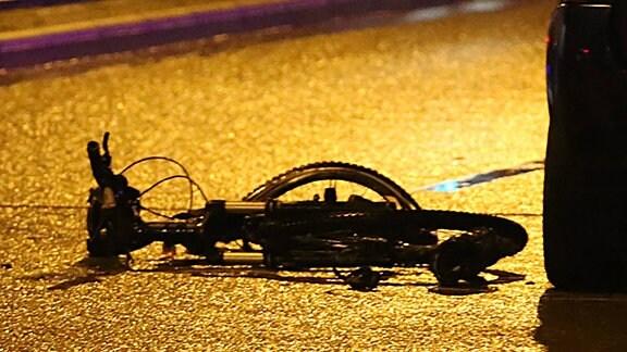 Fahrrad liegt nach einem Unfall auf einer nächtlichen Straße