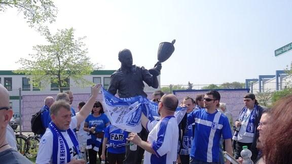Fans des FCM schmücken eine Statue vor dem Stadion.
