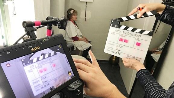 Eine Filmklappe und ein Kamera-Bildschirm.