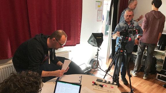 Teilnehmer des Film-Workshops bereiten am Set einen Dreh vor.
