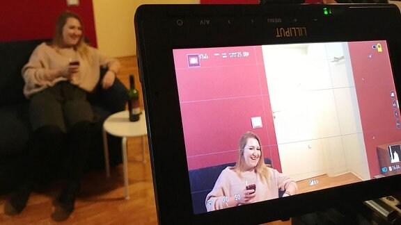 Ein Bildschirm, auf dem eine sitzende Frau zu sehen ist.