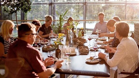 Menschen an einem gedeckten Tisch im Abendlicht.