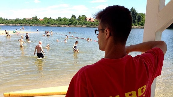 Ein junger Bademeister mit einem roten DLRG-Shirt schaut auf einen See mit Badegästen
