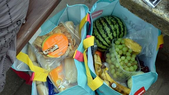 In zwei Einkaufstaschen sind mehrere Lebensmittel verstaut, darunter Weintrauben, Bananen und eine Melone