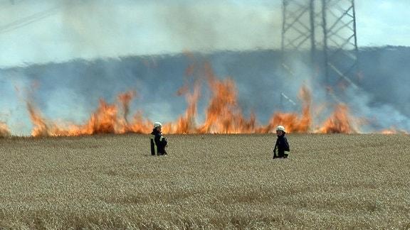 Zwei Feuerwehrmänner vor einem brennenden Feld
