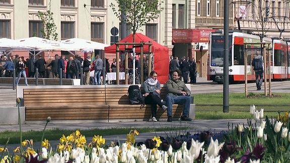 Zwei Menschen sitzen auf dem umgestalteten Steintorplatz in Halle auf einer Parkbank