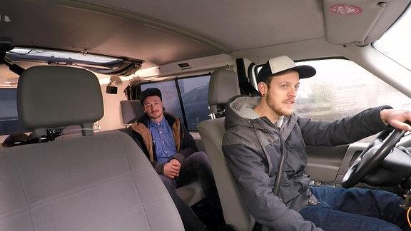 Zwei junge Männer sitzen in einem VW-Bus