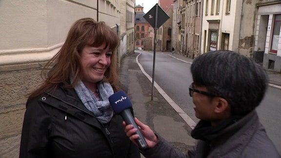 Eine Frau im Interview mit MDR-Reporter Duy Tran