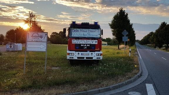 Ein Feuerwehrauto mit Plakaten steht bei Sonnenaufgang neben einer Straße.