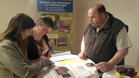 Drei Menschen beraten über Plänen an einem Tisch.