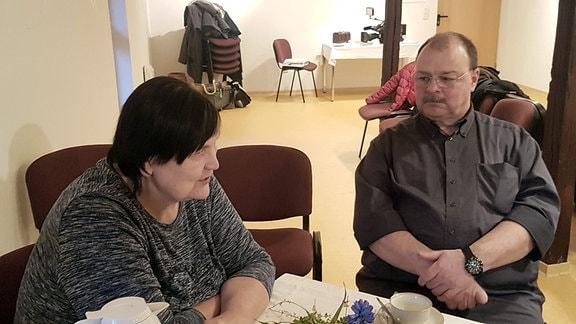 Eine Frau und ein Mann sitzen gemeinsam an einer Kaffeetafel.