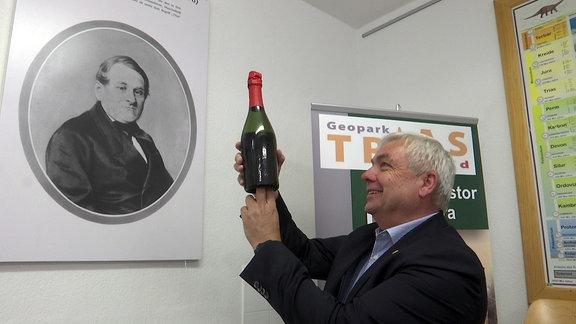Ein Mann hält eine Flasche Sekt in die Höhe