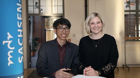MDR-Reporter Duy Tran und Charlotte Tennler neben einem MDR SACHSEN-ANHALT-Aufsteller.