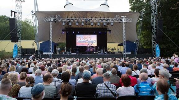 Menschen sitzen vor einer großen Bühne