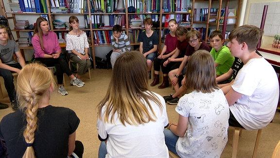 Schüler sitzen in einem Kreis