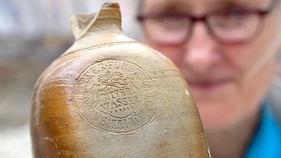 Archäologin Caroline Schulz hält eine Mineralwasserflasche aus Steingut vom Ende des 18.Jahrhunderts.