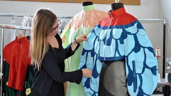 Eine junge Frau zupft eine Jacke zurecht, die an einer Modepuppe hängt