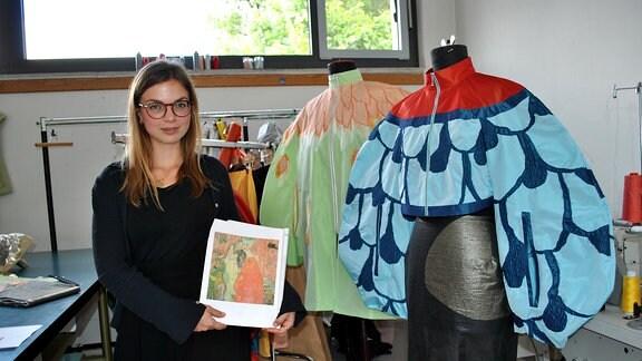 Eine junge Frau steht neben Modepuppen und hält eine Bild in den Händen
