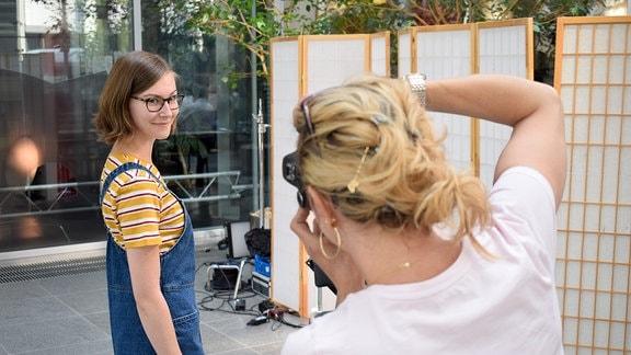 Eine junge Frau wird fotografiert.