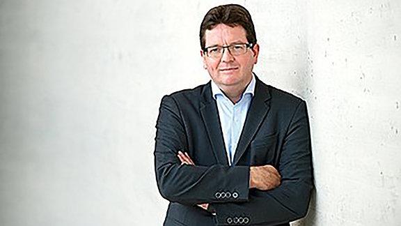 Ein dunkelhaariger Mann (Christian Tietje) mit Brille und Jacket
