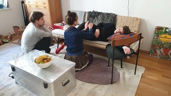 Eine Schwangere liegt auf einer Couch, eine junge Frau hält sie an der Hüfte.
