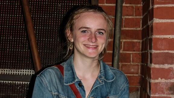 Eine junge Frau sitzt vor einem Haus