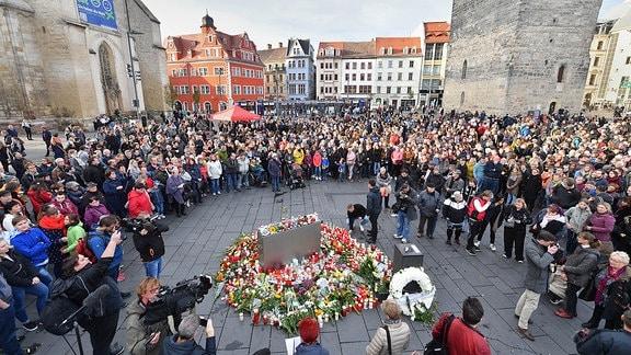 Menschen stehen auf dem Marktplatz von Halle neben Blumen und Kerzen