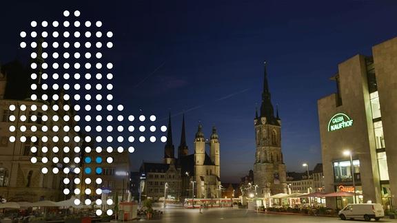 Blick auf den Marktplatz in Halle bei Dunkelheit, darauf eine Sachsen-Anhalt-Karte aus Punkten
