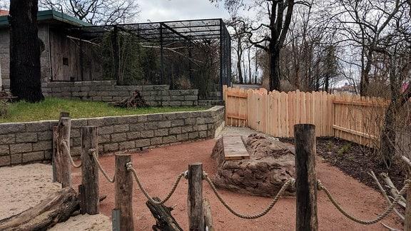 Eine begehbare Außenanalge in einem Zoo mit einer Sitzbank in der Mitte.
