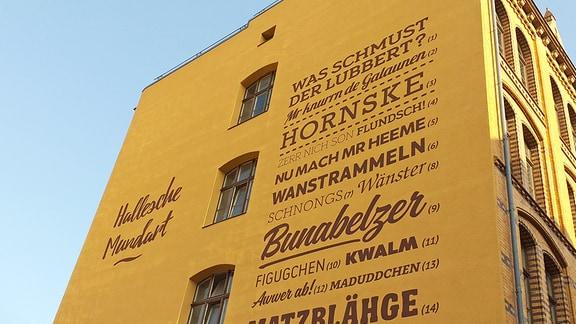 Wörter in hallescher Mundart, initiiert durch den Verein Pro Halle, an einer Hausfassade am Hallmarkt in Halle