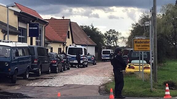 Polizeifahrzeuge an Ortsschild