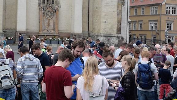 Mehrere Menschen spielen Pokémon GO auf dem Marktplatz in Halle