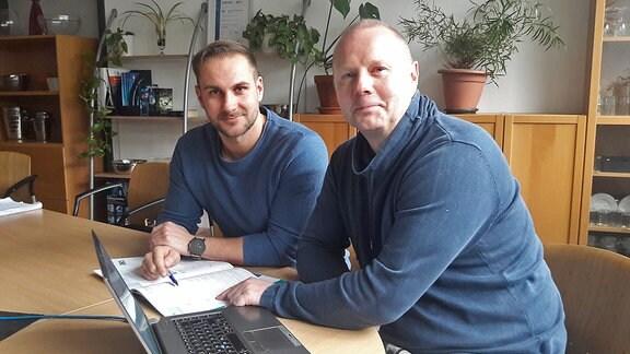 Zwei Männer, Stephan Dammköhler (links) und Florian Brode, sitzen an einem Laptop