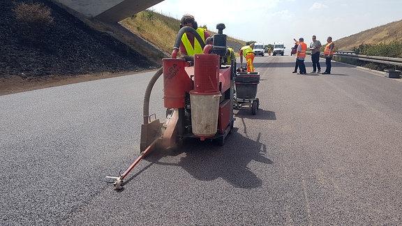 Bauarbeiter erneuern eine Fahrbahn auf einer Autobahn