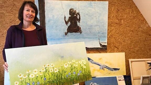 Malerin Heike Wolff aus Molmerswende mit einem Werk in der Hand